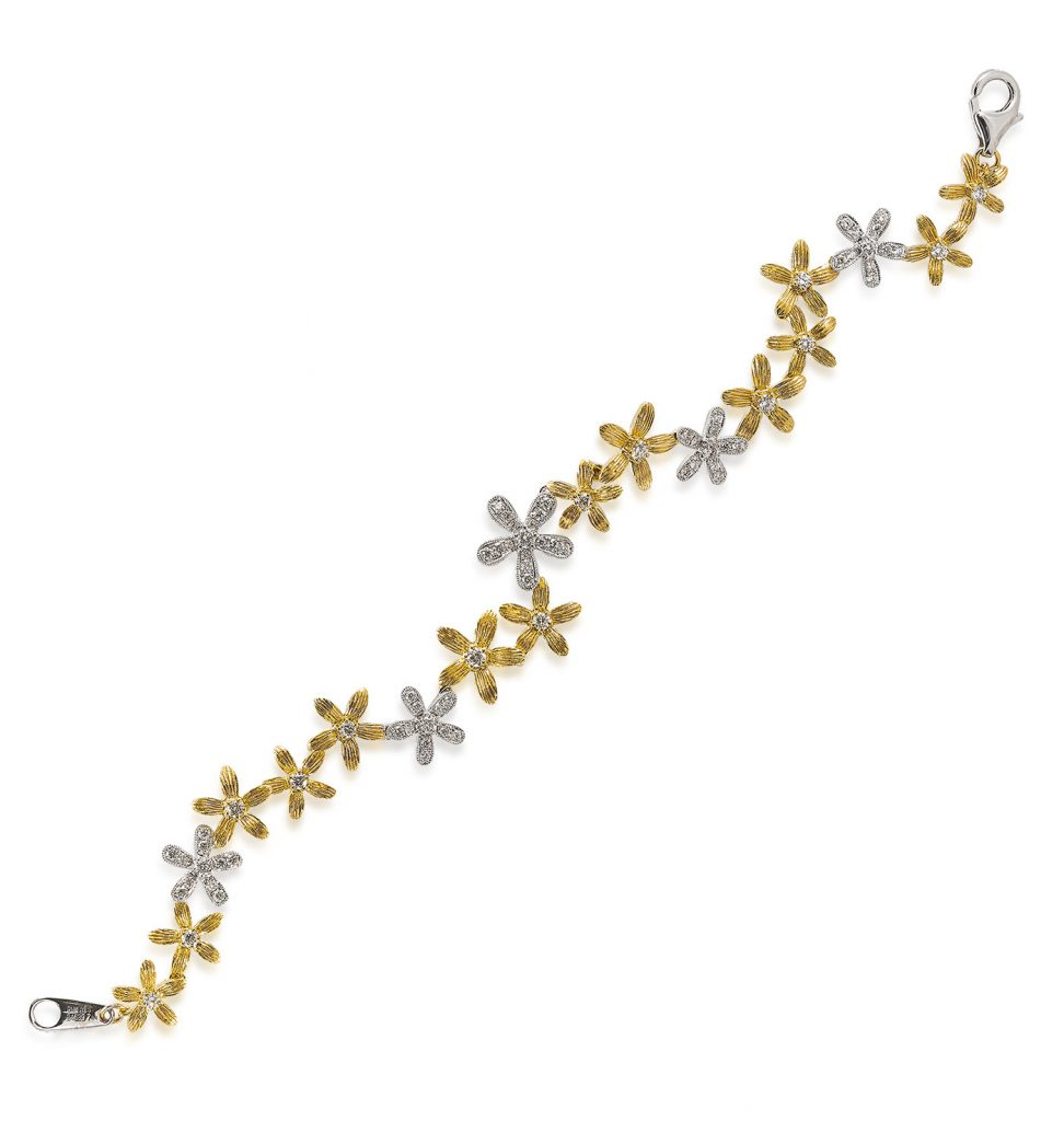 Jye's International two-tone daisy chain bracelet using 18K white gold and yellow brushed gold daisy links with diamond accents and milgrain border
