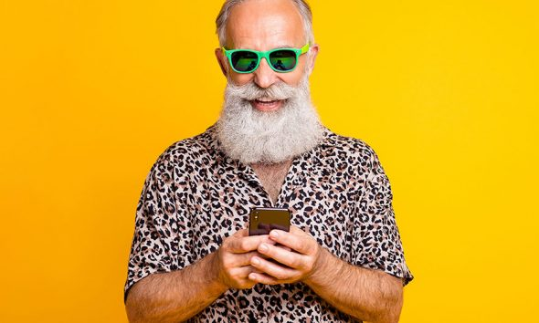 man wearing sunglasses holding phone