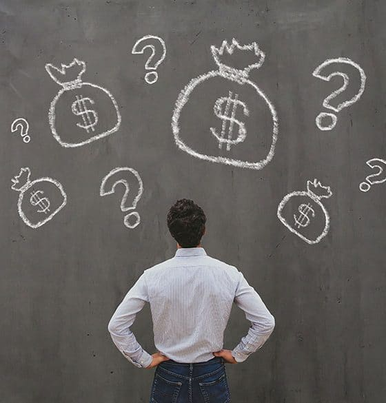 guy looking at dollar signs and question mark on the wall