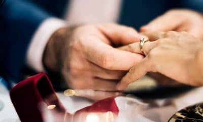 man's hand putting on engagement ring