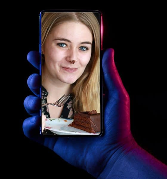 photo of lady on phone eating cake