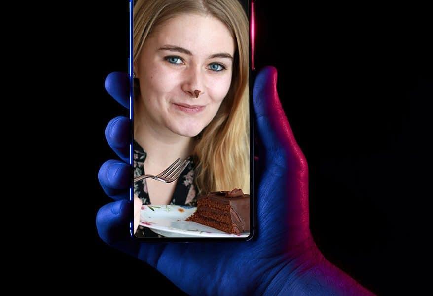 photo of lady on phone eating cake