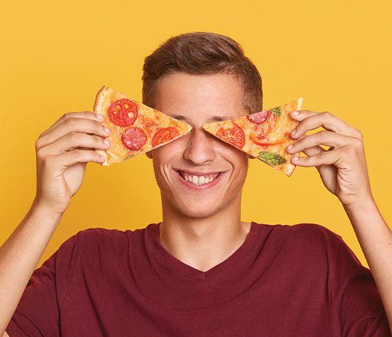 guy holds pizza on eyes